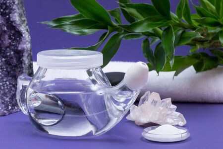 Spa purple background with Neti Pot, pile of Saline, rolled up White Towels, stacked Basalt Stones and Bamboo Leaves. Sinus wash. Nasal irrigation. Stok Fotoğraf