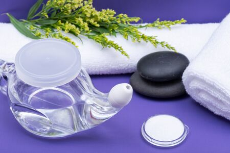 Spa purple background with Neti Pot, pile of Saline, rolled up White Towels and stacked Basalt Stones. Sinus wash. Nasal irrigation.