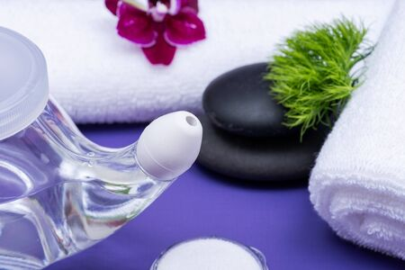 Spa purple background with Neti Pot, pile of Saline, rolled up White Towels, stacked Basalt Stones and Orchid Flower. Sinus wash. Nasal irrigation.