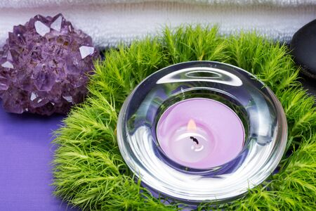 Wellness Relax concept with Spa elements. White Towels, Basalt Stones, Lavender Tea Light Candle, Dianthus Flowers and Amethyst on purple background.