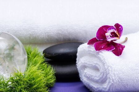 Wellness Relax concept with Spa elements. Rolled White Towels, Basalt Stones, Orchid, Clear Quartz Sphere and Dianthus Flowers on purple background.