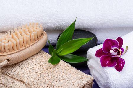 Concepto de bienestar spa. Esponja de lufa natural, cepillo de madera de cerdas naturales, toallas blancas, piedras de basalto, bambú y flor de orquídea sobre fondo morado. Foto de archivo