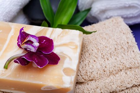 Spa Wellness Concept. Natural Loofah Sponge, Almond Goat's milk Soap, White Towels, Basalt Stones, Bamboo and Orchid Flower on purple background.