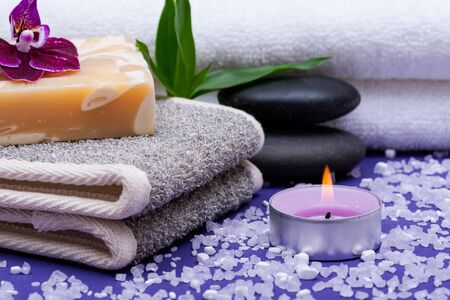 Spa Wellness Concept. Natural Back Scrubber,Goat's milk Soap, Basalt Stones, Orchid Flower, Bamboo and Lavender Tea Light Candle on purple background.