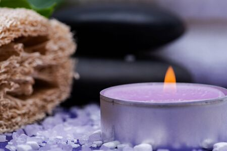 Spa Wellness Concept. Natural Loofah Sponge, stacked Basalt Stones, burning Lavender Tea Light Candle and sprinkled Epsom Salt on purple background.