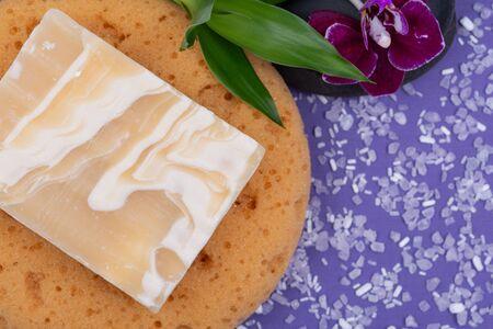 Spa Wellness Concept. Natural Foam Bath&Shower Sea Sponge, Almond Goat's milk Soap, Basalt Stones, Bamboo and Orchid Flower on purple background.