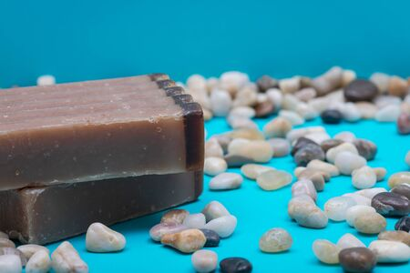 Handmade ultra-moisturizing Frankincense and Myrrh  Scented Goat's Milk Bar Soap decorated with small stone Pebbles on bright blue background.