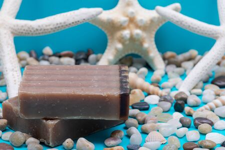 Handmade moisturizing Frankincense & Myrrh Goat's Milk Bar Soap decorated with small Pebbles, Sea Stars and Sea Shells on bright blue background.