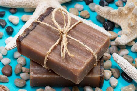Handmade moisturizing Frankincense & Myrrh Goat's Milk Bar Soap decorated with small Pebbles, Sea Stars and Sea Shells on bright blue background.
