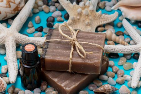 Handmade Frankincense & Myrrh Goat's Milk Bar Soap and Frankincense oil decorated with Pebbles, Sea Stars and Sea Shells on blue background.