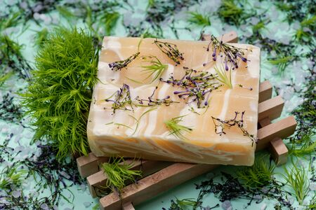 Wooden Soap Holder with Handmade ultra-moisturizing Almond Scented Goats Milk Bar Soap decorated with flower sprinkles confetti on green background.