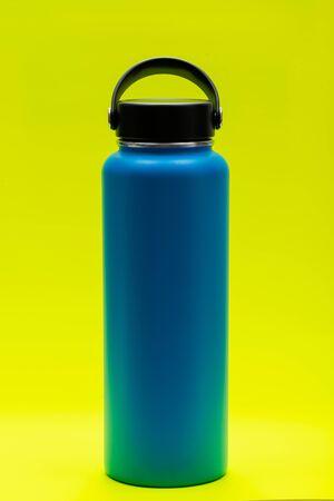 Botella de acero inoxidable aislada de boca ancha azul con tapa plana ancha aislada sobre fondo amarillo brillante. Sin BPA. Aislamiento al vacío de doble pared.