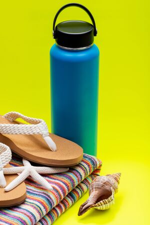 Blue Wide Mouth Insulated Stainless Steel Bottle, Women's Causal Flip Flops, Beach Towel, Starfish and Seashell on yellow background. Vacation concept. 写真素材