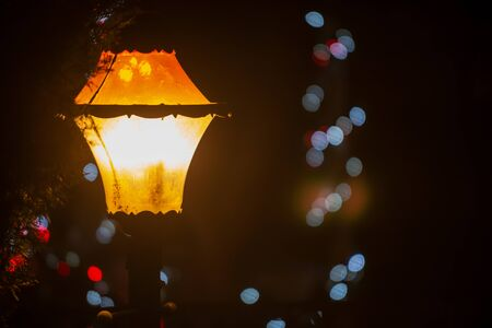 Vintage old style street light Lantern at night with Christmas decorations. Winter Holidays Tradition.