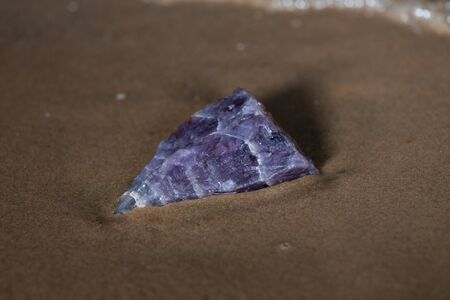 High grade rough natural Purple Auralite 23 Amethyst point from Canada on wet sand  in front of the lake at sunrise. Фото со стока