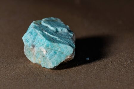 High grade rough natural Amazonite chunk from Madagascar on wet sand  in front of the lake at sunrise.