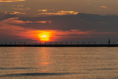 Silhouette of a walking man at a Pier at Sunrise with Sun reflecting in the Lake Michigan. Banque d'images - 128873684