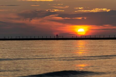 Silhouette of a walking man at a Pier at Sunrise with Sun reflecting in the Lake Michigan.
