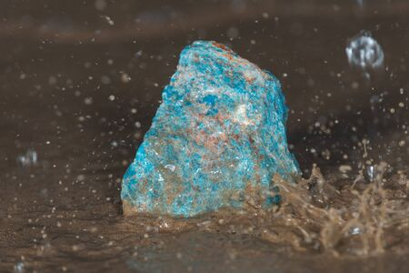 High grade rough natural Blue Apatite Specimen from Madagascar on wet sand  in front of the lake at sunrise.