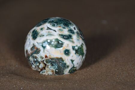 Orbicular Ocean Jasper sphere with crystallized vugs from Madagascar on wet sand  in front of the lake at sunrise. Фото со стока