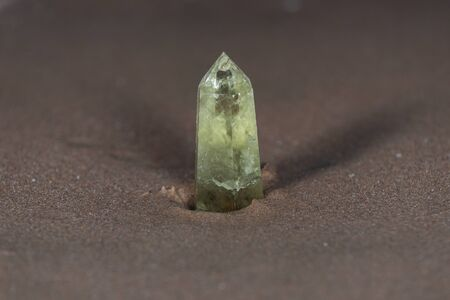 Polished CITRINE single point on wet sand  in front of the lake at sunrise. Stock fotó
