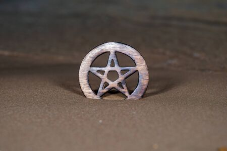Wooden encircled Pentagram symbol on the beach at sunrise in front of the lake. Concept of Five elements: Earth, Water, Air, Fire, Spirit. Фото со стока