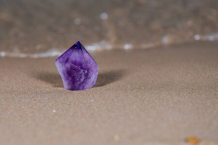Large Amethyst Phantom  Point from Brazil on wet sand on the beach at sunrise.