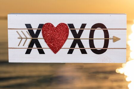 XOXO Hugs and Kisses wooden sign with Red Heart at the sunrise in front of the lake. Love, Romance and Friendship concept.