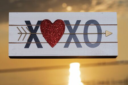 XOXO Hugs and Kisses wooden sign with Red Heart at the sunrise in front of the lake. Love, Romance and Friendship concept. 免版税图像 - 128873638