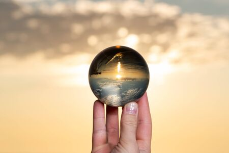 Woman's hand holding high grade Clear Quartz Sphere at the sunrise in front of the lake.
