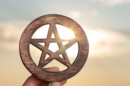 Womans hand holding Wooden encircled Pentagram symbol at sunrise in front of the lake. Concept of Five elements: Earth, Water, Air, Fire, Spirit. Stock fotó