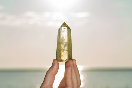Woman holding Polished CITRINE point in her hand at sunrise in front of the lake.
