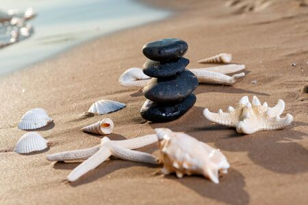 Spa composition - stacked Basalt Stones, Seashells and Sea Stars on the beach at sunrise in front of the ocean. Wellness, Balance and Relax concept. Banque d'images - 128873546