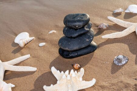 Spa composition - stacked Basalt Stones, Seashells and Sea Stars on the beach at sunrise in front of the ocean. Wellness, Balance and Relax concept. Stock fotó