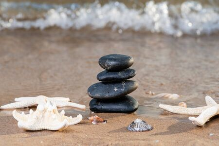 Spa composition - stacked Basalt Stones, Seashells and Sea Stars on the beach at sunrise in front of the ocean. Wellness, Balance and Relax concept. Фото со стока