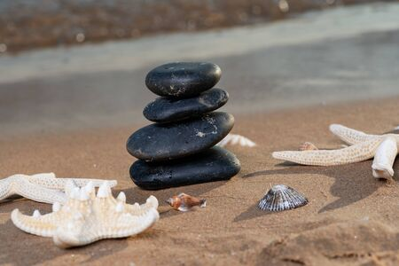 Spa composition - stacked Basalt Stones, Seashells and Sea Stars on the beach at sunrise in front of the ocean. Wellness, Balance and Relax concept. Banque d'images