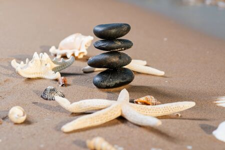 Spa composition - stacked Basalt Stones, Seashells and Sea Stars on the beach at sunrise in front of the ocean. Wellness, Balance and Relax concept. Banque d'images - 128873521