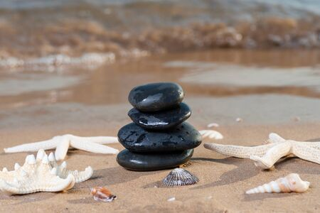 Spa composition - stacked Basalt Stones, Seashells and Sea Stars on the beach at sunrise in front of the ocean. Wellness, Balance and Relax concept. Stockfoto