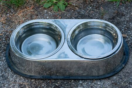Stainless steel Bowls with Fresh Water for Thirsty Dogs put outdoors on the sidewalk where people walk with their pets on hot summer day.