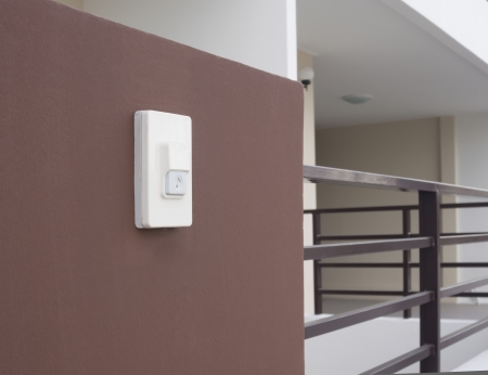 door bell ring plate with music note sign on brown wall