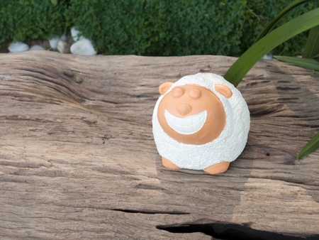 little sheep garden decorative statue on the log Stock Photo - 17902729
