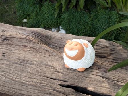 little sheep garden decorative statue on the log Stock Photo