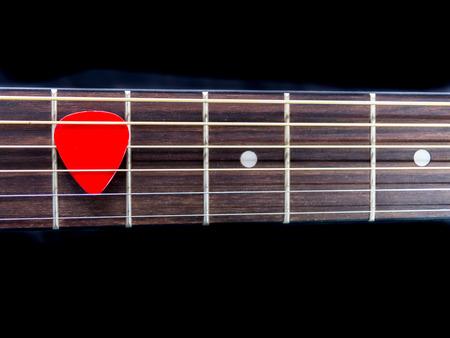 Pick guitar on finger board background