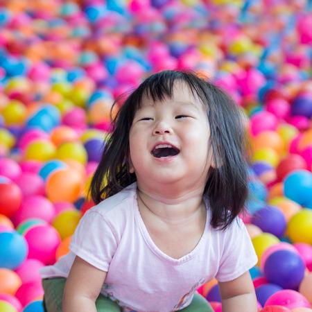 Asia niña feliz que juega con las bolas Foto de archivo - 58107645