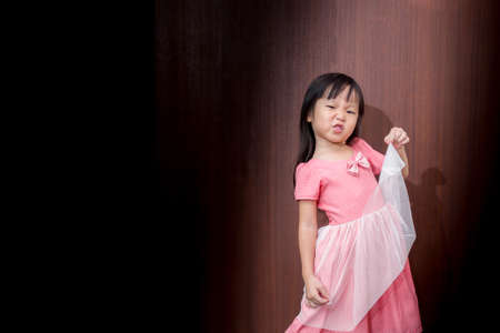shorten: Portrait of a little Asian kid girl , Made to shorten mouth Stock Photo