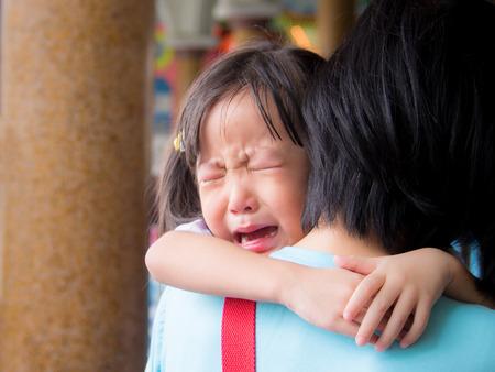 Bebé asiático que abraza a su madre llorando Foto de archivo