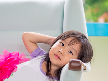 laying down: Beautiful young girl child laying down on a white sofa at home, asian girl