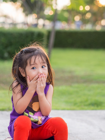 Little asian girl covering her mouth with her hands. Surprised or scared. Stock Photo