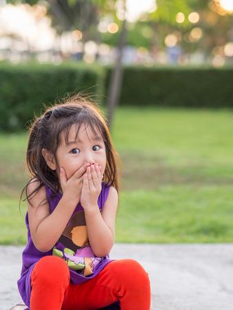Niña asiática que cubre la boca con las manos. Sorprendido o asustado. Foto de archivo