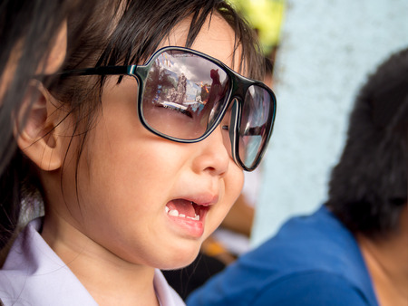 forgetful: Little Asian girl starts crying , sunglasses Stock Photo